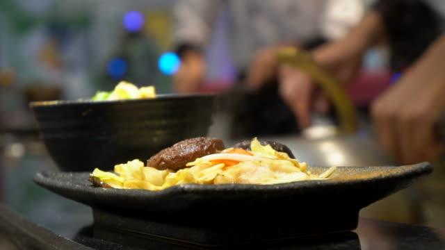 vidéos et rushes de chef qui dessert frais steak avec légumes grillés au restaurant - plat