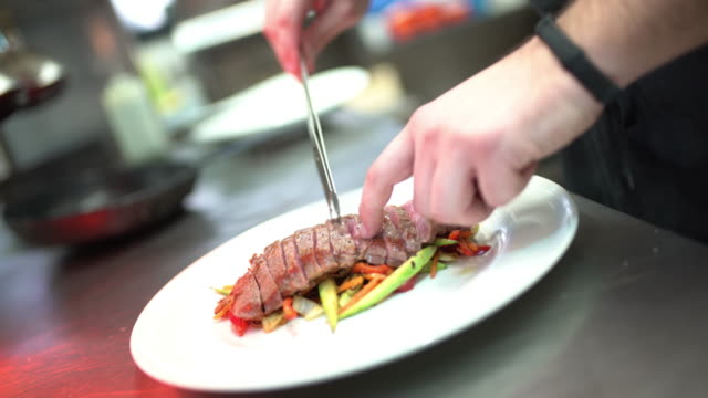 Chef serving sliced steak meal.