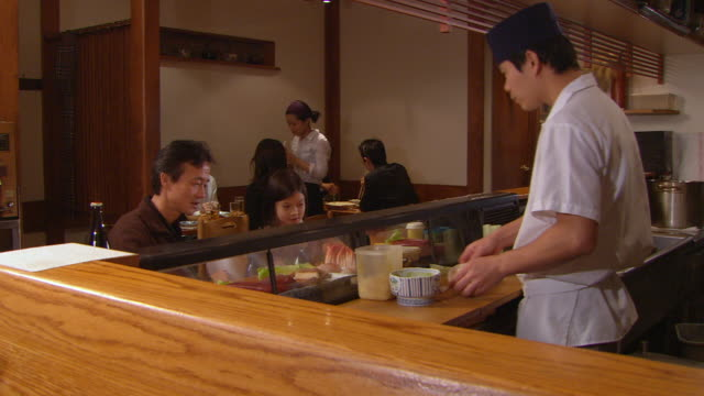 ms, chef serving sushi to man with daughter (10-11) - 少於10秒 個影片檔及 b 捲影像