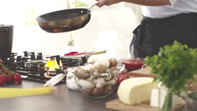 chef shaking skillet, mixing tomatoes and garlic - stove stock videos & royalty-free footage