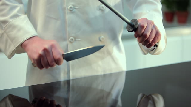chef sharpening kitchen knife - kitchen knife stock videos & royalty-free footage