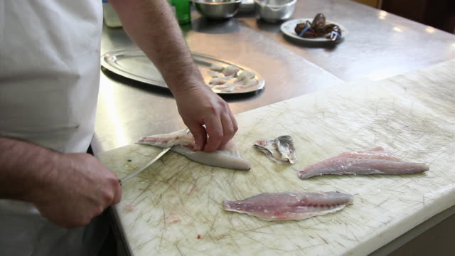 Chef slices carpaccio of raw fish