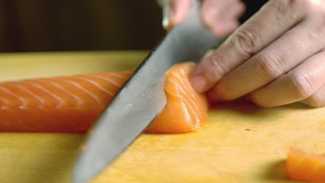 vídeos de stock e filmes b-roll de chef slicing some salmon sashimi in kitchen bar at the japanese restaurant - cortado em filete