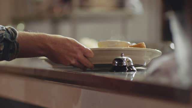 chef slides plates on kitchen counter, rings bell and male waiter picks up food to deliver to customers - hart arbeiten stock-videos und b-roll-filmmaterial