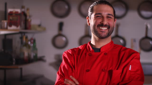 A chef smiles in his kitchen.