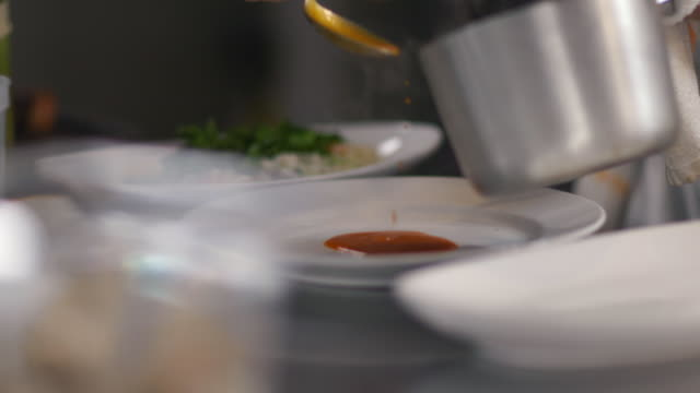 Chef spoons steaming sauce on clean dinner plate in restaurant kitchen