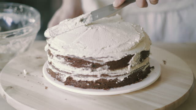 chef spread cream on model cake - icing stock videos and b-roll footage