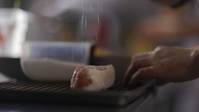 chef sprinkles salt over steak on grill in restaurant kitchen - sprinkling stock videos and b-roll footage