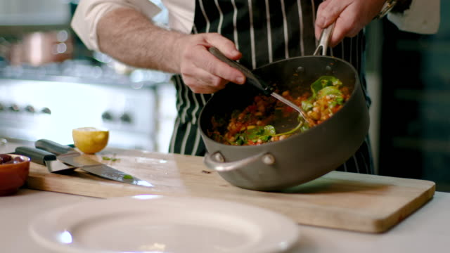 chef stirs healthy vegetables in a saucepan before plating - vegetarian food stock videos & royalty-free footage