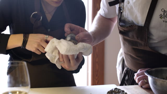 chef teaching a student how to remove meat from an oyster - dishcloth stock videos & royalty-free footage