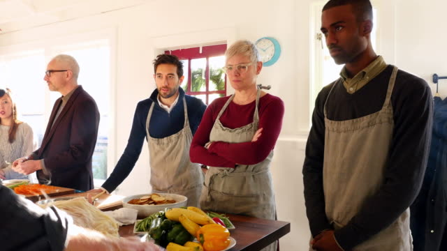vidéos et rushes de ms pan chef teaching group of friends how to prepare turkey during cooking class - enseigner