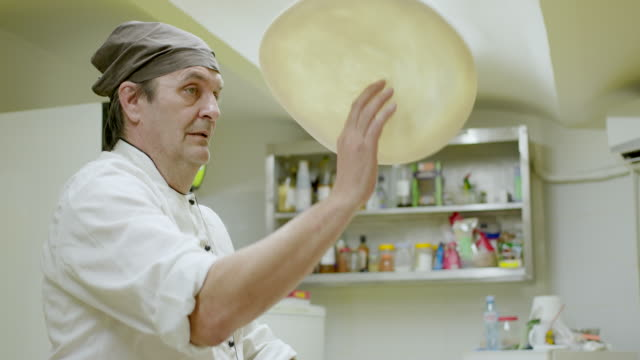 chef throwing pizza dough in the air with one hand - smooth stock videos & royalty-free footage