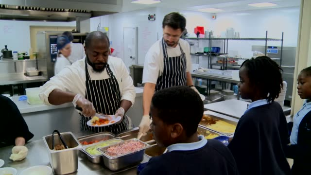 'chef to school' charity aims to cut the cost of contract caterers england london int sliced carrots in trays jerk chicken in bowl chicken poured... - pointing stock videos & royalty-free footage