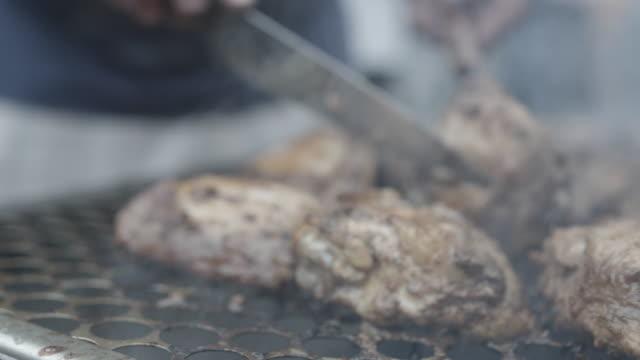 chef tosses chicken on grill, slow motion - pollo alla brace video stock e b–roll