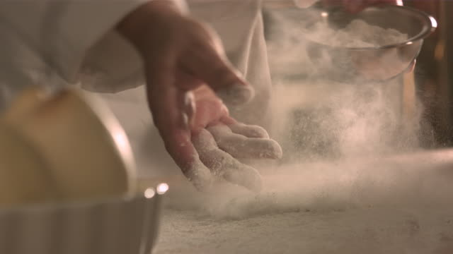 chef tossing flour onto kitchen table. - flour stock videos & royalty-free footage