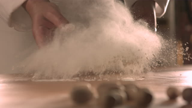 chef tossing flour onto kitchen table. - bakery stock videos and b-roll footage