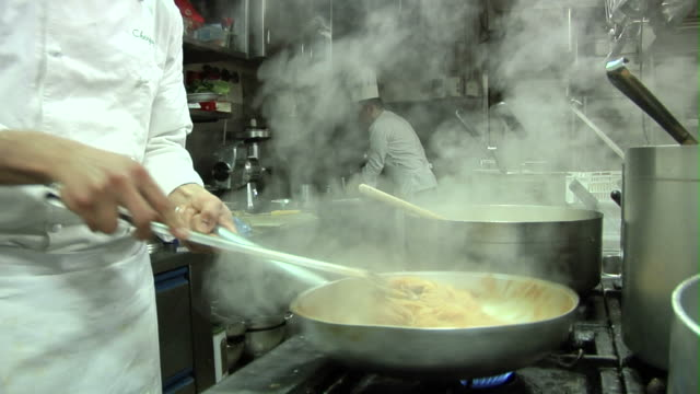 SLO MO, CU, Chef tossing pasta from frying pan, mid section
