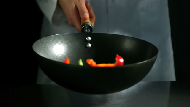 Chef tossing wok of sliced peppers