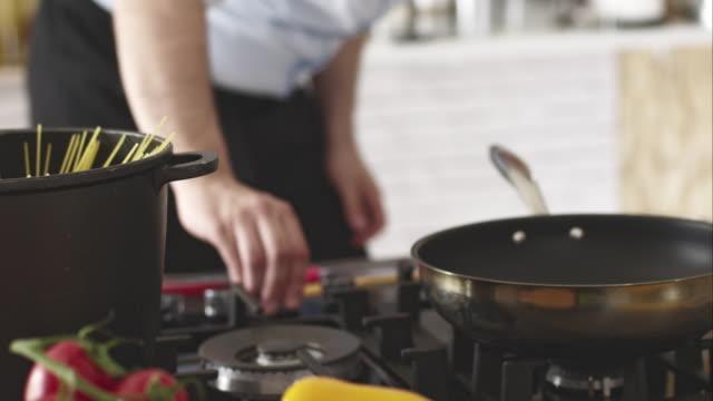 capocuoco girando sul gas stufa, preparare un pasto