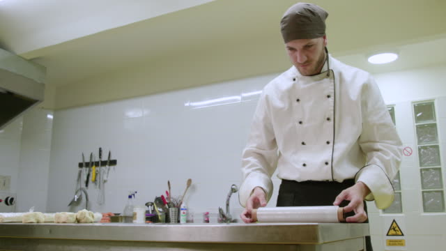 chef unfolding and cutting plastic foil on kitchen counter - trainee stock videos & royalty-free footage