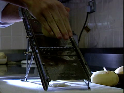 chef uses a grater to thinly slice potatoes to make crisps - grater utensil stock videos & royalty-free footage