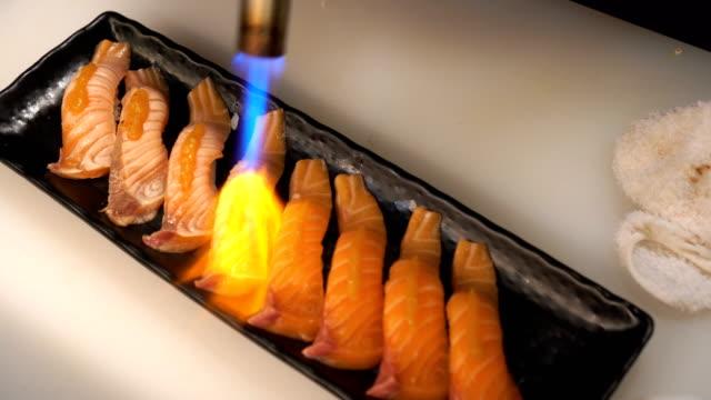 vídeos de stock, filmes e b-roll de chef, usando uma tocha flamejante queima sushi de salmão - comida japonesa