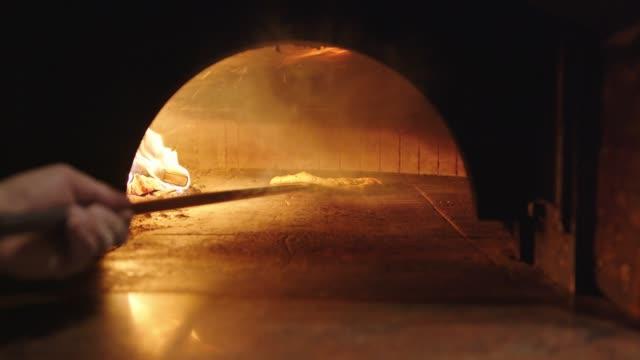 vídeos de stock, filmes e b-roll de chef usando uma casca para se mover em torno do cozimento da pizza no forno a lenha - firewood