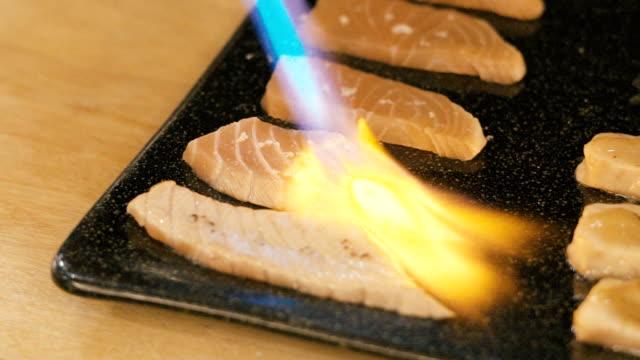 Chef using a torch burn salmon sushi.