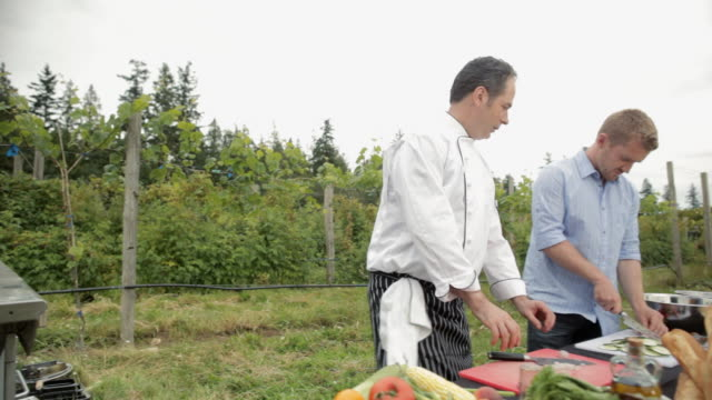chef using grill and men preparing food for outdoors dinner party - farm to table stock videos & royalty-free footage