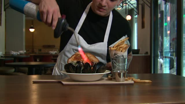 wgn chef using torch on moules frites at french bistro cochon volant in chicago on december 1 2015 - french food stock videos and b-roll footage