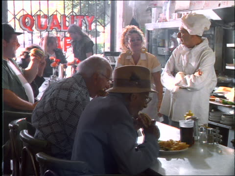 Chef + waitress behind counter with people eating in diner