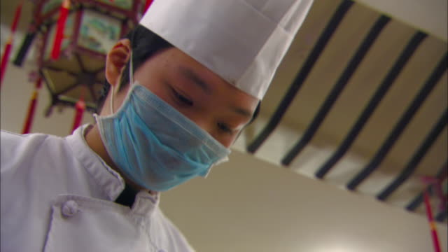 a chef wears a mask over his mouth as he prepares food. - 料理人点の映像素材/bロール
