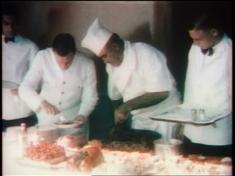 1936 chef with hat + assistants preparing plates of food at buffet table on ocean liner cruise - 少於10秒 個影片檔及 b 捲影像