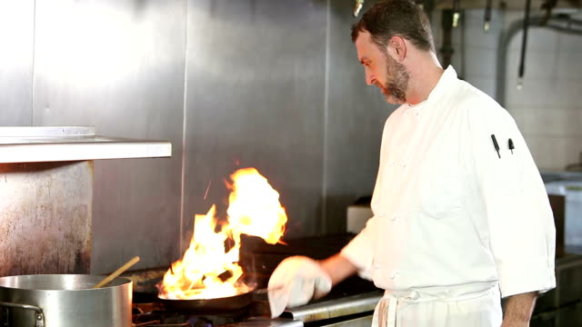 Koch mit heiß brennenden Topf in Großküchen