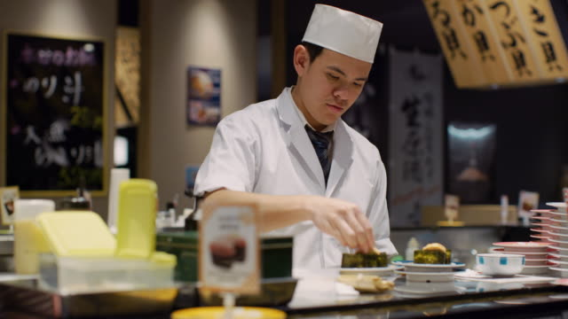 ms a chef works in a sushi restaurant / tokyo, japan - 料理人点の映像素材/bロール