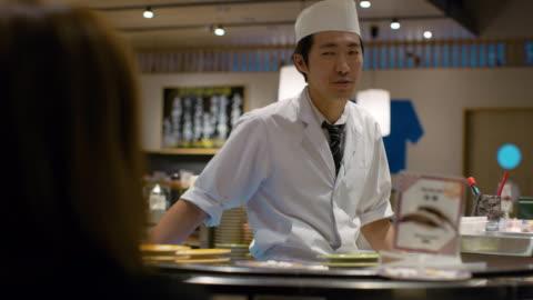stockvideo's en b-roll-footage met ms a chef works in a sushi restaurant / tokyo, japan - klanten georiënteerd
