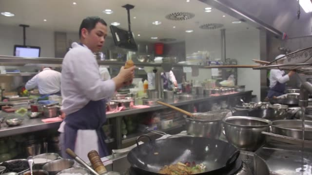 chefs cooking in kitchen at the park chinois restaurant in mayfair london united kingdom on friday jan 22 chef cooking food in wok food frying in wok... - food state stock videos & royalty-free footage