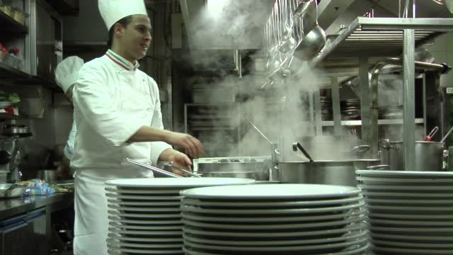vídeos de stock e filmes b-roll de t/l, cu, zi, chefs cooking in restaurant kitchen - stack