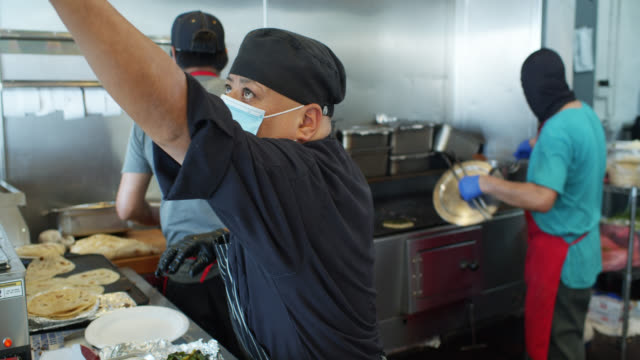 vídeos de stock e filmes b-roll de chefs cooking mexican cuisine wearing masks and gloves at work during covid-19 lockdown - jantar comida e bebida