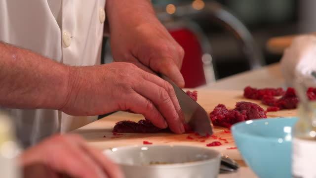 chefs cut beef to make steak tartare - steak tartare stock videos and b-roll footage