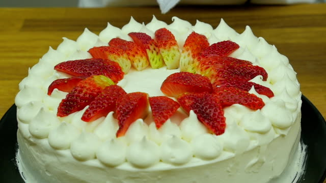 chef's decorating cake with strawberry slow motion