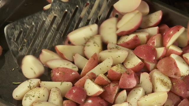 vidéos et rushes de cu, chef's hand seasoning sliced potatoes in roast dish - pomme de terre rouge