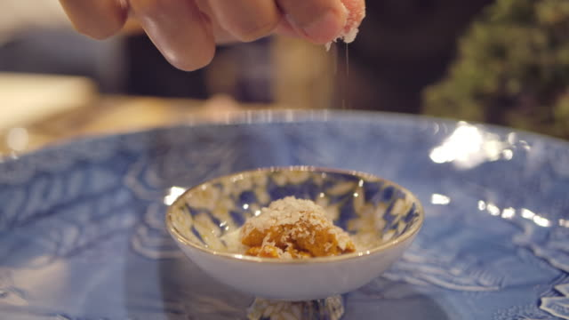 chef's hand sprinkles salt seasoning over uni japanese dish in omagase restaurant kitchen - foodie stock videos & royalty-free footage
