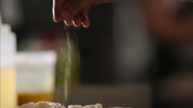 chef's hand sprinkles seasoning over scallops on grill in restaurant kitchen - gewürz stock-videos und b-roll-filmmaterial