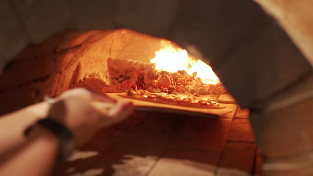 chefhand pizza in den lehmofen nehmen - back lit stock-videos und b-roll-filmmaterial