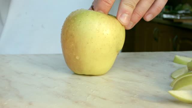 Nos chefs mains de couper une pomme verte fraîche.