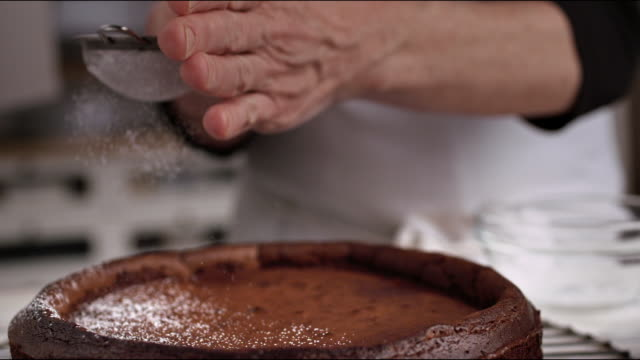 chefs hands sprinkling powdered sugar on top of flourless chocolate cake recipe - sprinkling stock videos and b-roll footage