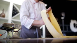 Chef's hands use a pasta cutting machine. Fresh spaghetti pasta coming out of pasta machine close-up, slow mo