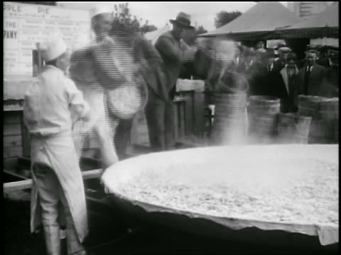 B/W 1929 chefs pouring apples into world's largest pie outdoors / Albion, NY / newsreel