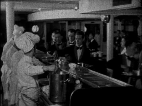 B/W 1930 chefs serving soup as waiters put bowls on trays in kitchen of ocean liner / educational